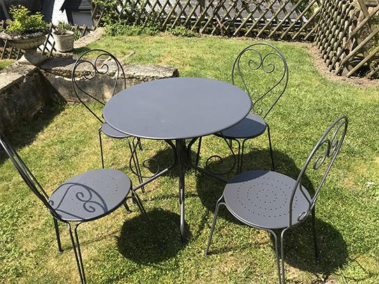 Salle à manger de jardin en métal façon fer forgé GUERMANTES: une table et 4 fauteuils empilables anthracites